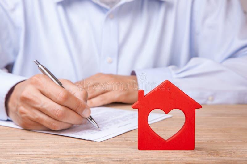 Försäkring, hyra eller köp för begrepp hem- Det röda huset med hjärta och mannen undertecknar avtalet royaltyfri bild