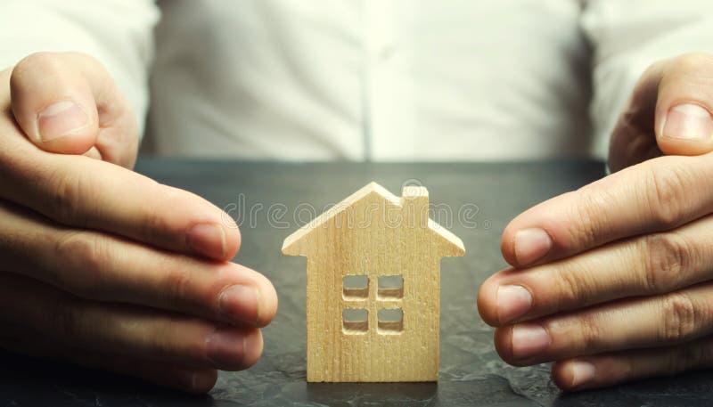 Försäkringmedlet skyddar huset med en gest av skydd Begreppet av skydd och hus för egenskapsförsäkring arkivfoto