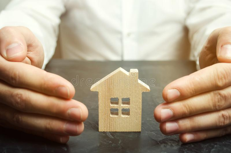 Försäkringmedlet skyddar huset med en gest av skydd Begreppet av skydd och hus för egenskapsförsäkring arkivbilder