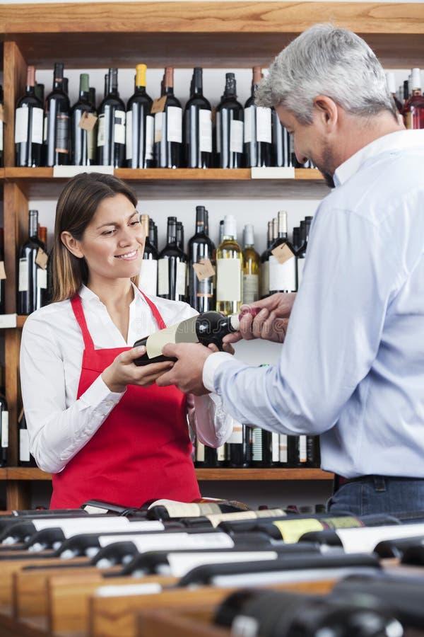 Försäljare Giving Wine Bottle till den manliga kunden arkivbilder