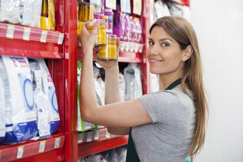 Försäljare Holding Food Cans vid hyllor i älsklings- lager arkivfoto