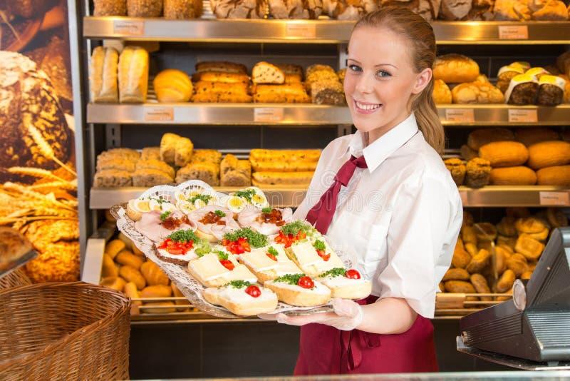 Försäljare i bageri som framlägger smörgåsar till kunden royaltyfri fotografi