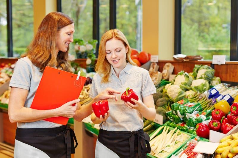 Försäljare i utbildning som får hjälp från personalen royaltyfria foton