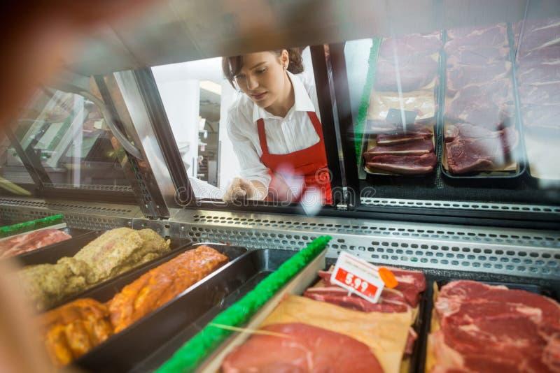 Försäljare Looking At Variety av kött som in visas arkivfoton