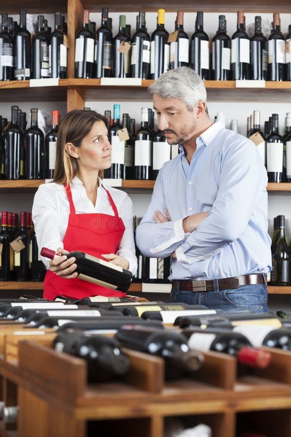 Försäljare Showing Wine Bottle till den manliga kunden arkivfoto