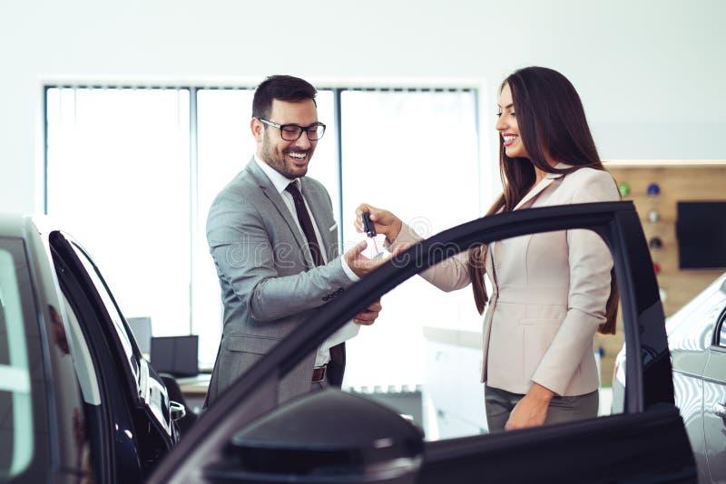 Försäljare som ger tangenter av den nya bilen till den manliga klienten royaltyfri fotografi