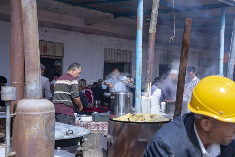 Försäljare som säljer mat på den Kashgar söndag boskapmarknaden, Kina arkivfoto