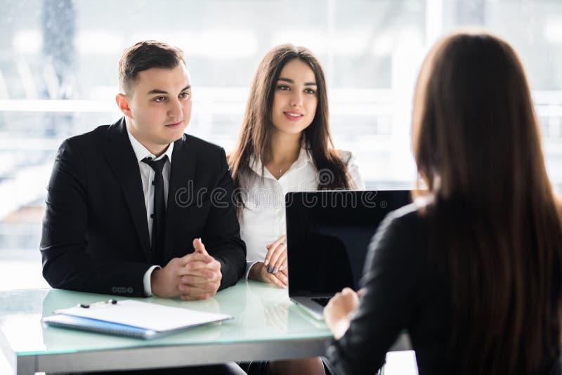 Försäljare som talar med ett par av lyckliga kunder som sitter i ett skrivbord på kontoret Consalting par för chef i regeringsstä arkivfoton