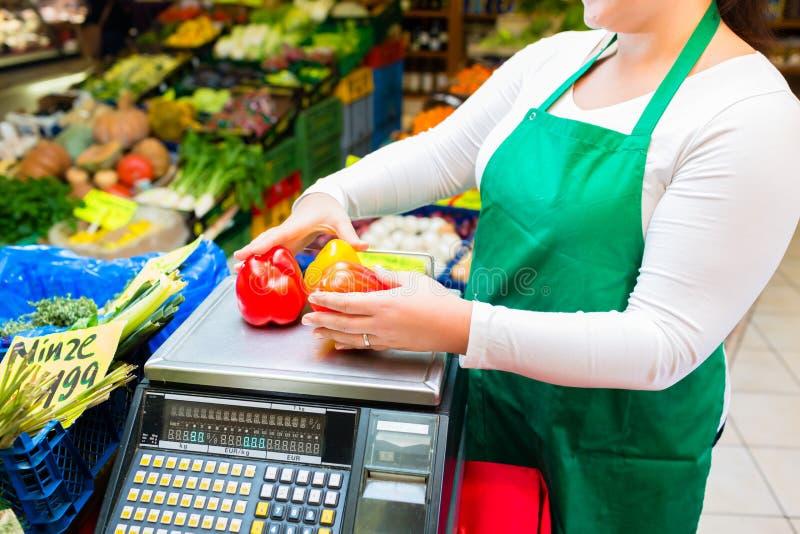 Försäljare som väger grönsaker på skala i specerihandlare royaltyfria bilder