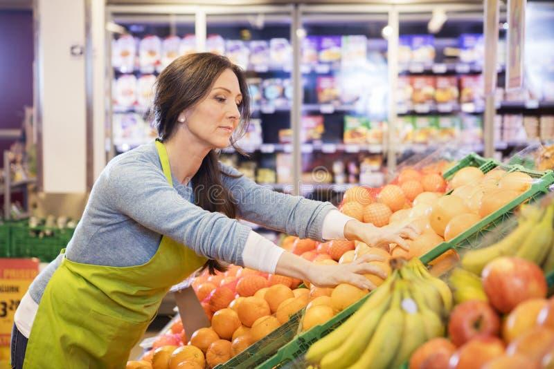 FörsäljareArranging Oranges In supermarket arkivbild