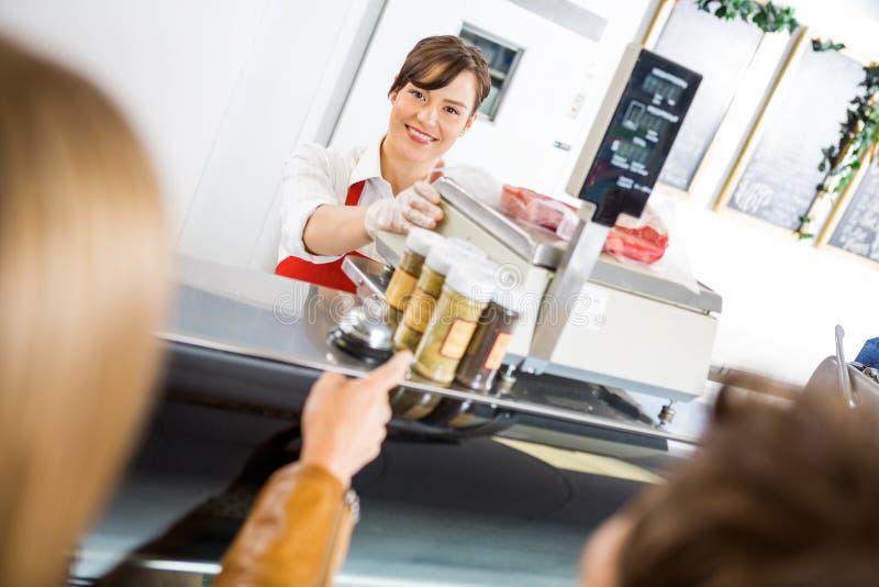 FörsäljareAt Counter Attending kunder in royaltyfri fotografi