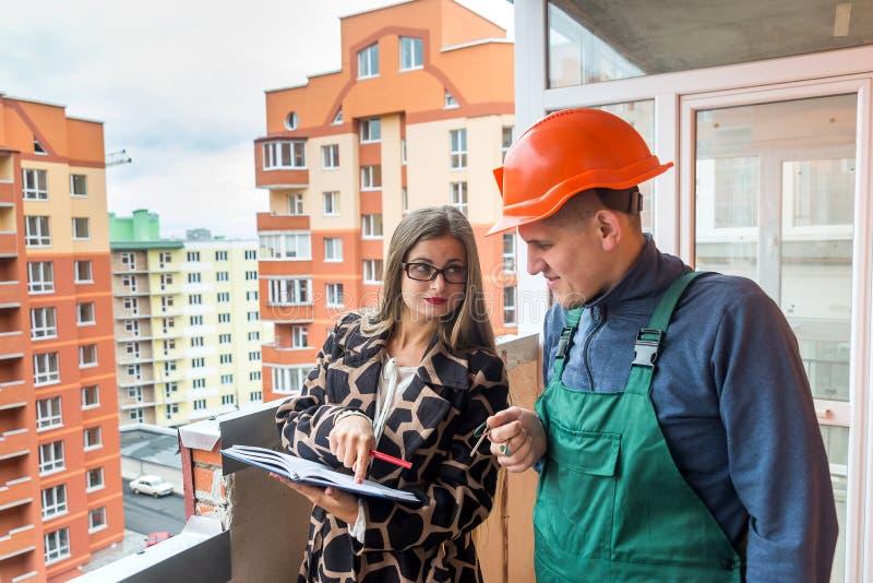 Försäljarehandstil i notepaden och byggmästaren som nära står fotografering för bildbyråer