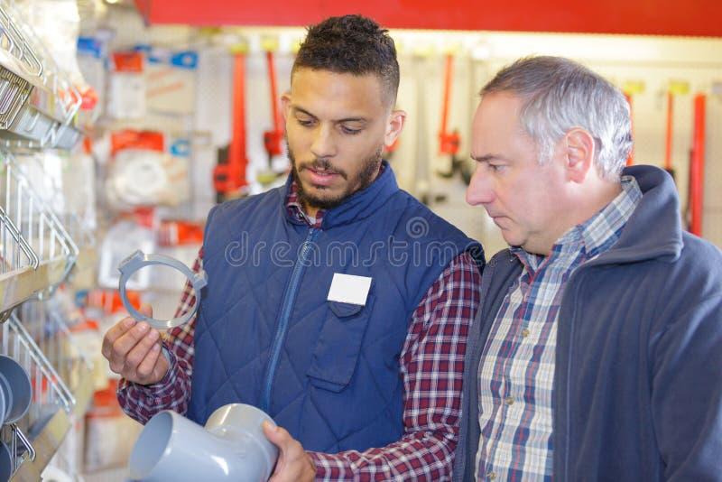 Försäljaren i maskinvara shoppar med klienten royaltyfria foton