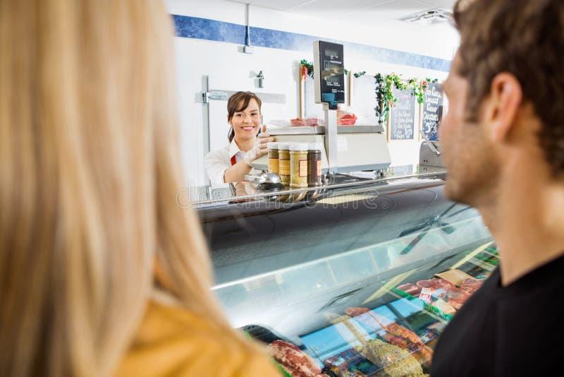 Försäljaren Looking At Customers i slaktare shoppar arkivbild