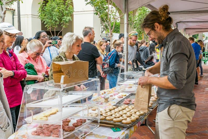 Försäljaren på den i stadens centrum Los Angeles munkfestivalen tjänar som strikt vegetarianmunkar till den stora folkmassan fotografering för bildbyråer