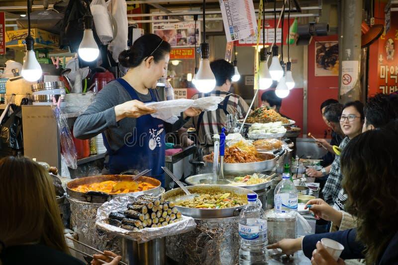 Försäljareportionkunder i Gwangjang matmarknad royaltyfri foto