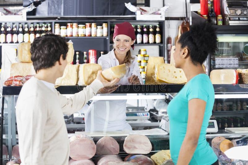 FörsäljareSelling Cheese To par i livsmedelsbutik royaltyfria bilder