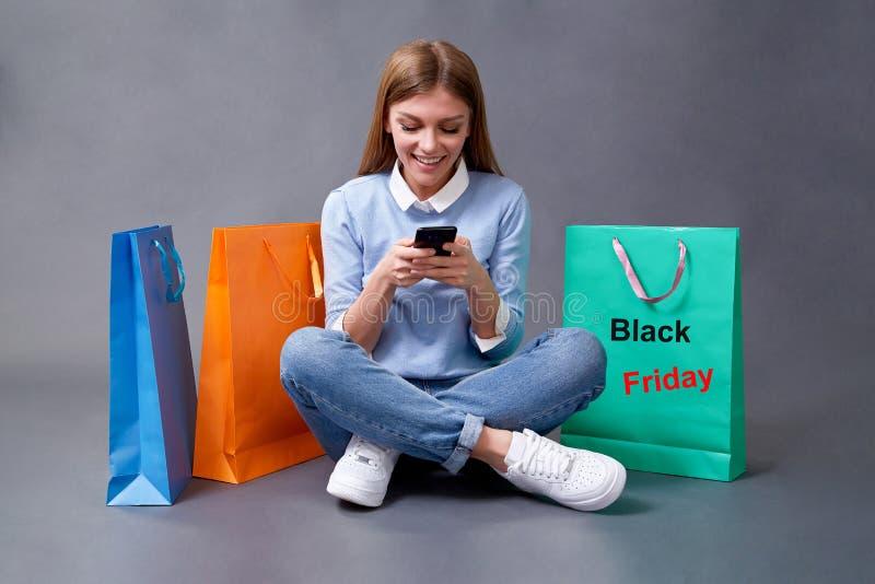 Försäljning, köp, rabatt och Black Fredag-koncept Svart fridag Kvinnor med shoppingväskor royaltyfria bilder