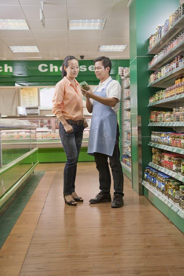 Försäljningar är kontorist att hjälpa kvinnor som undersöker kruset i supermarket, Peking royaltyfria foton