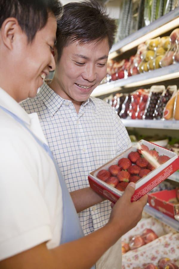 Försäljningar är kontorist att hjälpa mannen i supermarket, Peking arkivfoton