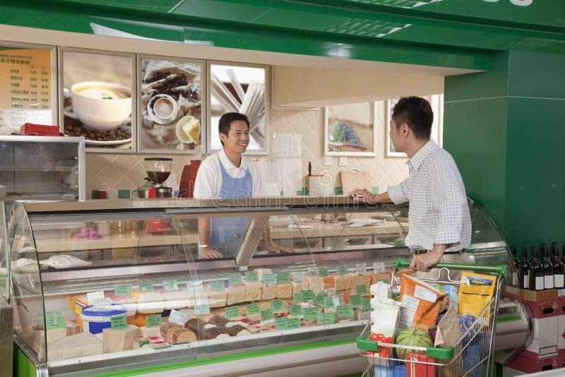 Försäljningar är kontorist att le, och hjälpa mannen på delikatessaffären kontra i supermarket royaltyfri fotografi