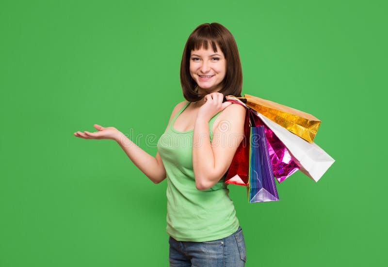 försäljningar Lycklig ung flicka med färgrika shoppingpåsar som isoleras på fotografering för bildbyråer