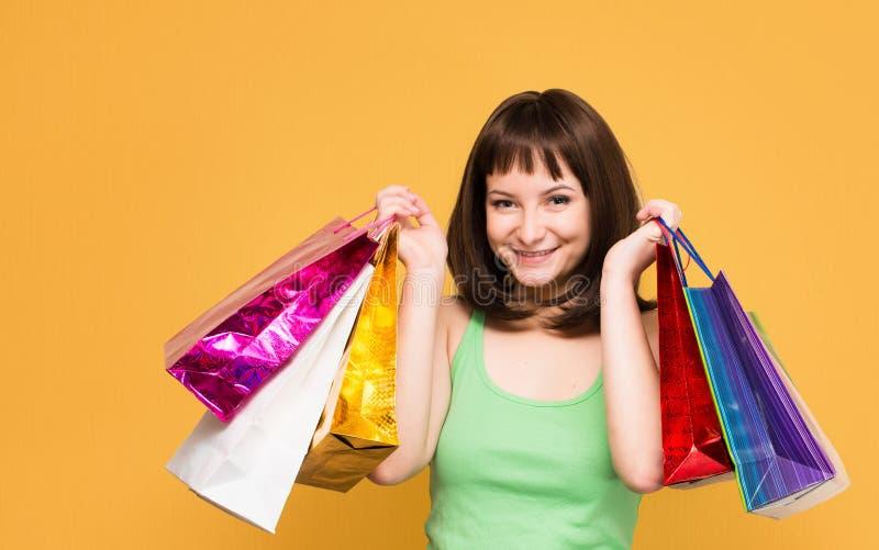 försäljningar shoppare Lycklig ung flicka med färgrik iso för shoppingpåsar royaltyfri foto