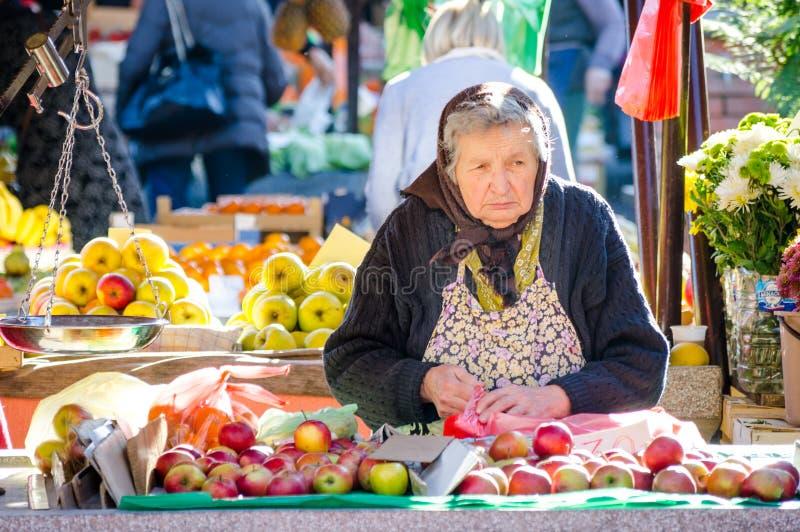 Försäljningsäpplen och blommor för gammal dam på marknadsstället royaltyfri fotografi