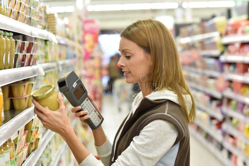 Försäljningsassistent i livsmedelsbutikscanningprodukter royaltyfri foto