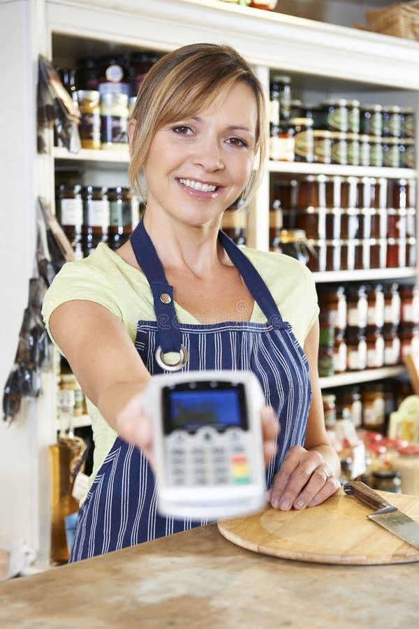 Försäljningsassistent i matlager som räcker kreditkortmaskinen till Cus arkivfoto