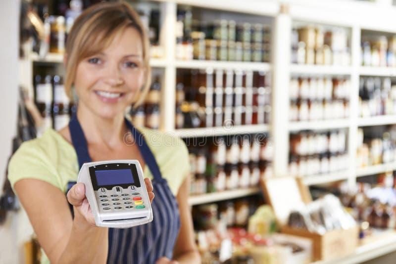 Försäljningsassistent i matlager som räcker kreditkortmaskinen till Cus royaltyfri fotografi