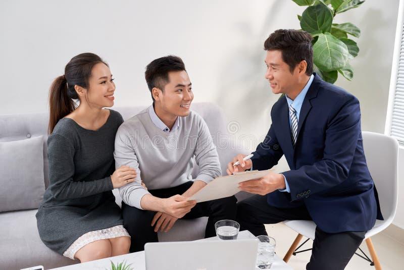 Försäljningskonsulent som visar nya investeringsplaner till unga asiatiska par royaltyfri fotografi