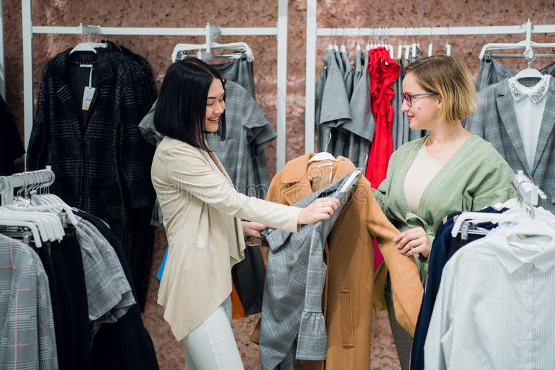 Försäljningskonsulentportionen väljer kläder för kunden i lagret Shoppa med stylistbegrepp kvinnlign shoppar arkivfoton