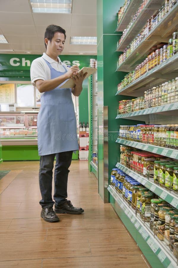 Försäljningskontorist som kontrollerar varor i supermarket royaltyfri foto