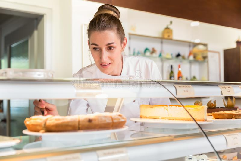 Försäljningskvinnan i bageri shoppar sätta kakor på skärm arkivbild