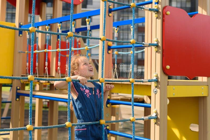 Försök för tonårs- flicka till att klättra på repväggen Hon spelar med repväggen för att framkalla motoraktivitet på lekplatsen arkivfoto