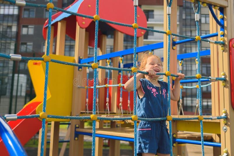 Försök för tonårs- flicka till att klättra på repväggen Hon spelar med repväggen för att framkalla motoraktivitet på lekplatsen royaltyfria bilder