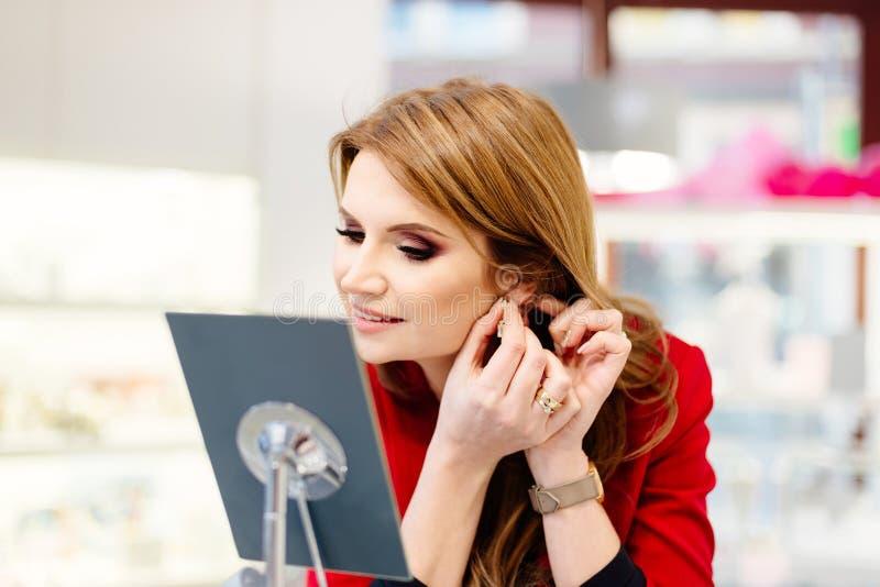 Försökande örhängen för ung skönheteleganskvinna i smyckenlagret arkivbild