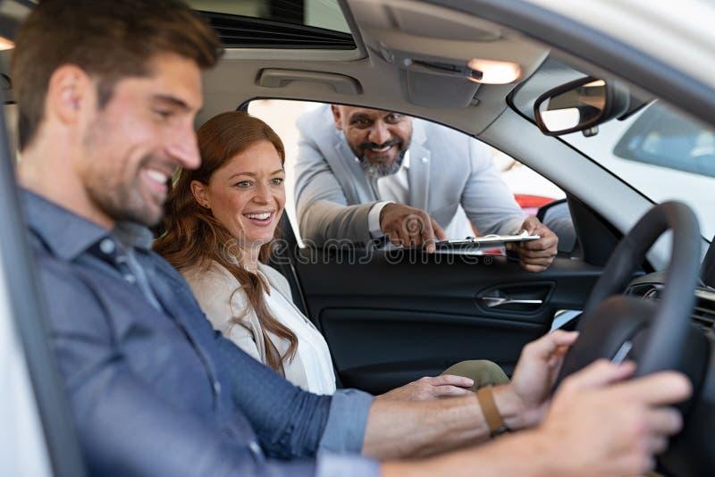 Försökande bil för par på återförsäljaren arkivbild