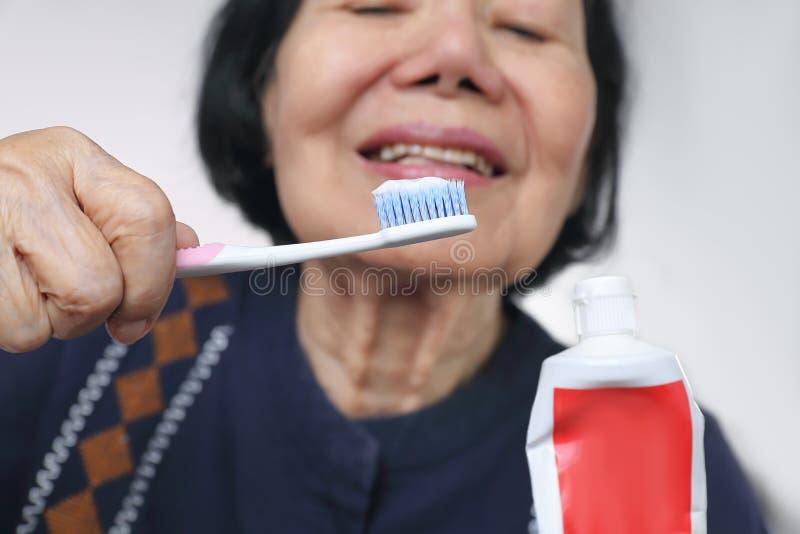 Försökande brukstandborste för asiatisk äldre kvinna tand- royaltyfria foton