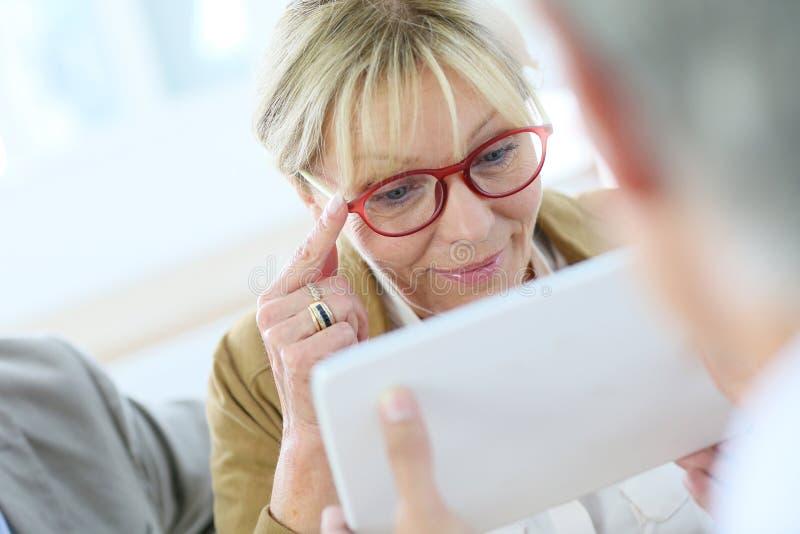Försökande glasögon för hög kvinna royaltyfria bilder