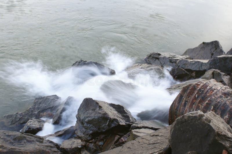 Förse med kloaker urladdning in i floden royaltyfri foto