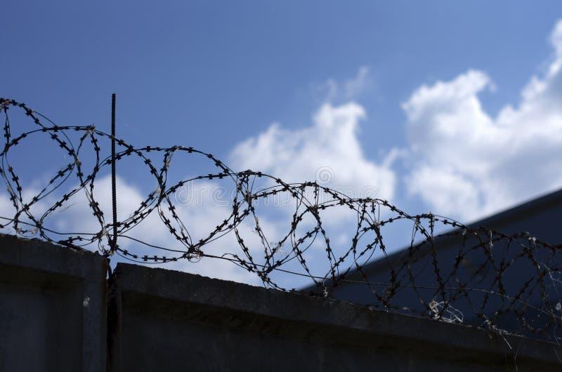 Försedd med en hulling metall - tråd över det konkreta staketet arkivfoto