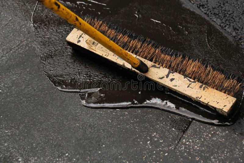 Försegla en skadad asfaltdrevväg arkivbilder