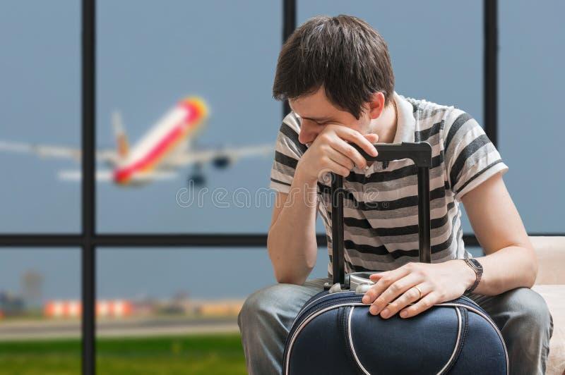 Försenat flygplanbegrepp Den trötta passageraren sitter med bagage i flygplats royaltyfri foto