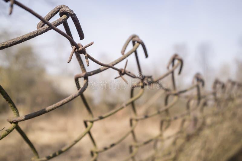 Försett med en hulling gammalt rostigt staket av metallingreppet och - tråd royaltyfria bilder