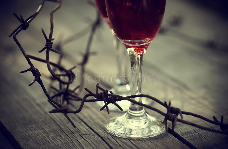 Försett med en hulling rostigt - tråd och exponeringsglas med rött vin arkivfoto