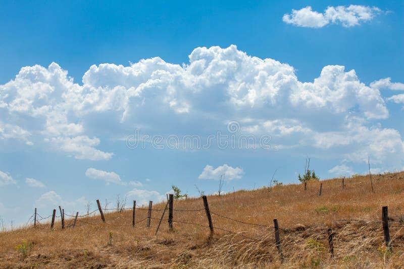 Försett med en hulling - tråd Fenceline och blå himmel arkivbild