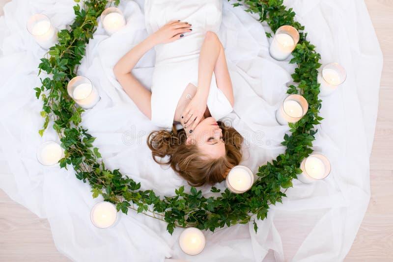 Försiktig övresikt på en blyg liggande flicka som hänsynsfullt trycker på hennes hals, hennes dolde ögon, smutsigt naturligt hår  royaltyfri foto