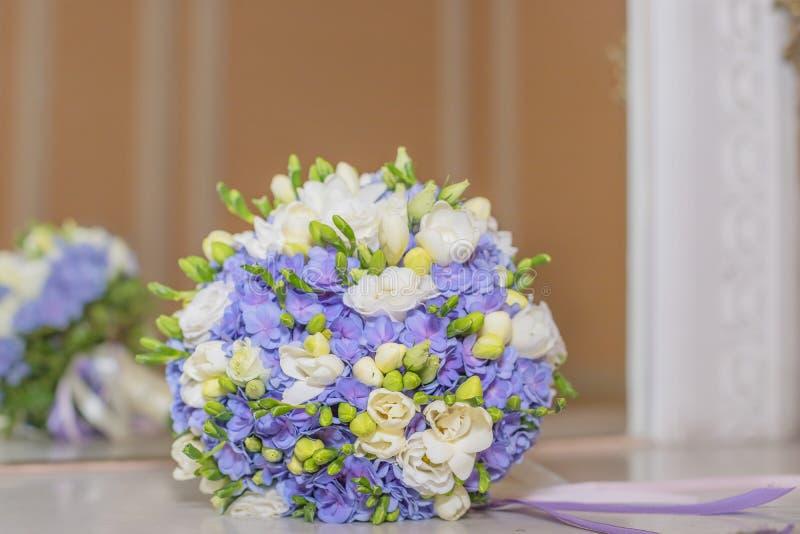 Försiktig bröllopbukett av vanliga hortensior, rosor och freesia på en vit pastellfärgad bakgrund Gifta sig detaljer i blått och  royaltyfria bilder